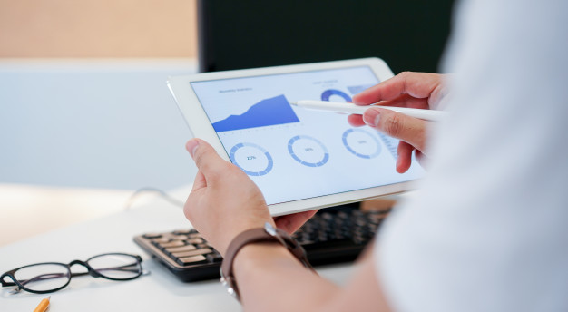 businessman-using-pen-planning-financial-strategy-tablet-with-dashboard_42708-871